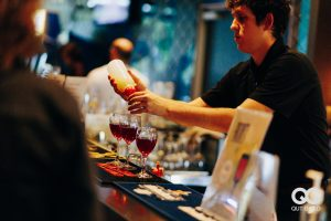 A bartender pours into three glasses of red drinks. He is making a Reset Cocktail.
