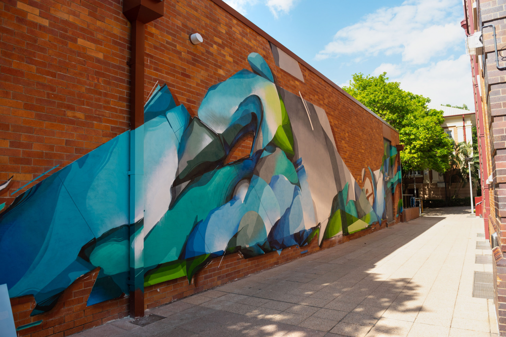 Green, Blue and Grey street art mural on a brick wall