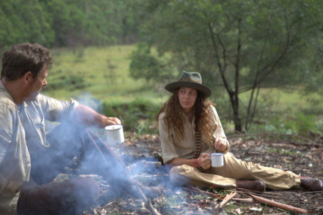 White man at campfire, adjecent, Jarrah (woman) drinks from a cup