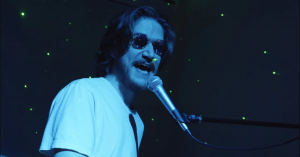 Bo Burnham in a dark room at his piano mic with seedy sunglasses on.