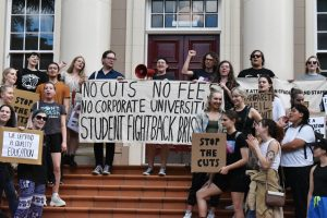 About 20 students stand on steps of building in front of door, holding placards. Sign in centre reads: No cuts, no fees, no corporate universities, Students Fight Back Brisbane. Sel Dowd holds a microphone, centre.