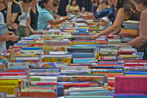 hundreds of books on a table with people picking and browsing