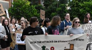 """Crowd of young people holding placards, front and centre reading """"Stop the attacks on students and staff""""."""