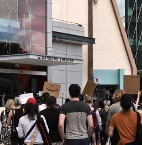 """Students march past theatre, marked by a sign as """" Garden's Theatre"""". Students hold placards that can not be read from behind."""