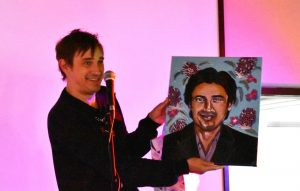 Magenta background. Trent Dalton (man) stands behind microphone on stage, holding a self portrait.