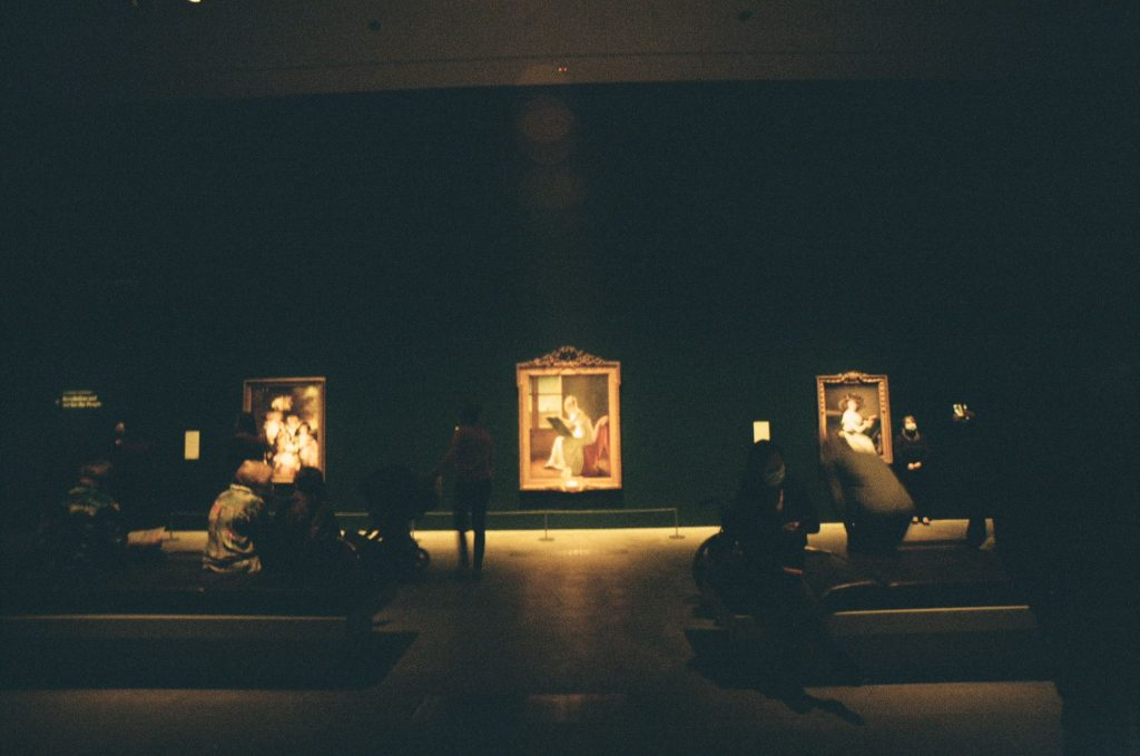 Exhibition paintings on the wall at GOMA. People sitting and standing look on.